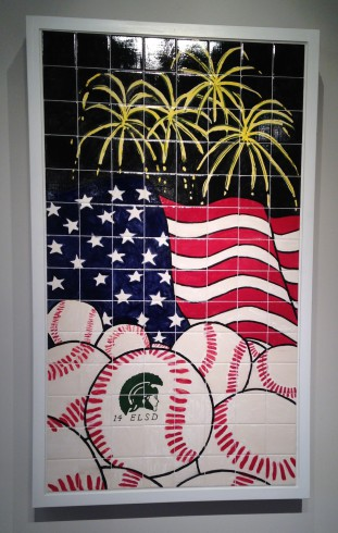 Image of artwork made from black tile with the American flag, yellow fireworks, and a pile of Little League baseballs.