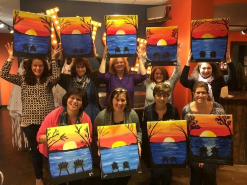 A group of people gather to show off their artwork created at a Paint Party
