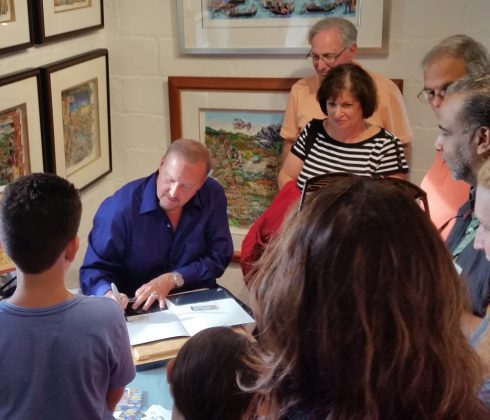 Charles Fazzino in his studio at Arts Fest drawing while fans look on