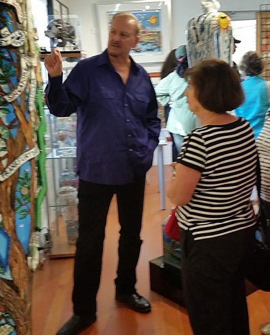 Charles Fazzino in his studio at Arts Fest describing his artwork to a fan