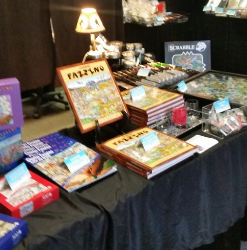 Stacks of Fazzino books, puzzles, gift cards and more on a table at Arts Fest