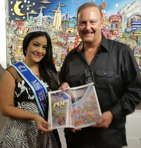 Charles Fazzino and Miss Westchester Briana Coralys holding up the Arts Westchester Magazine