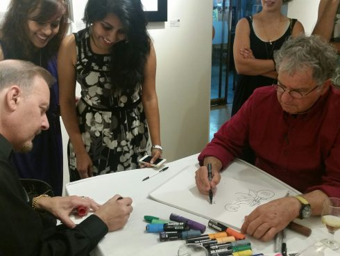 Charles Fazzino and David Gerstein working on drawings while onlookers smile with intrigue