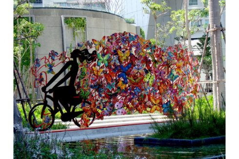 David Gerstein installation of a bicyclist with a colorful trail set in a park