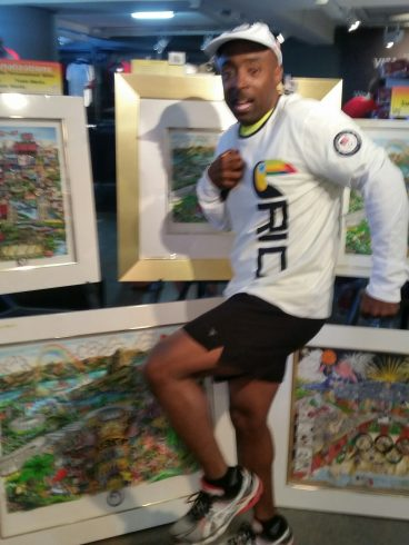 A man in a white long sleeved shirt and black shorts posing in front of the Fazzino's 2016 Olympic Games collection.