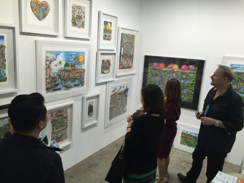 Charles Fazzino looking at his 3d Pop Art work with fans in Korea