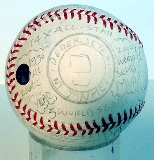 Writing with pencil on a baseball to create art