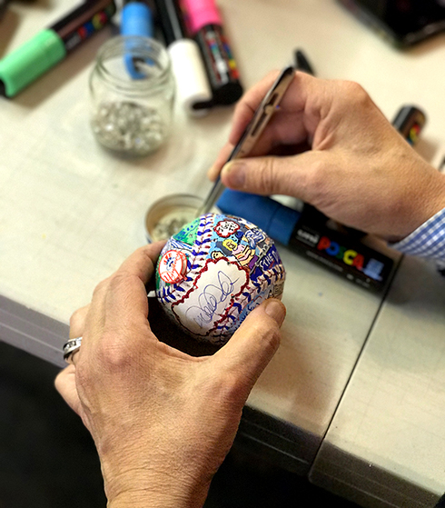 Charles Fazzino adds crystals to decorate the baseball