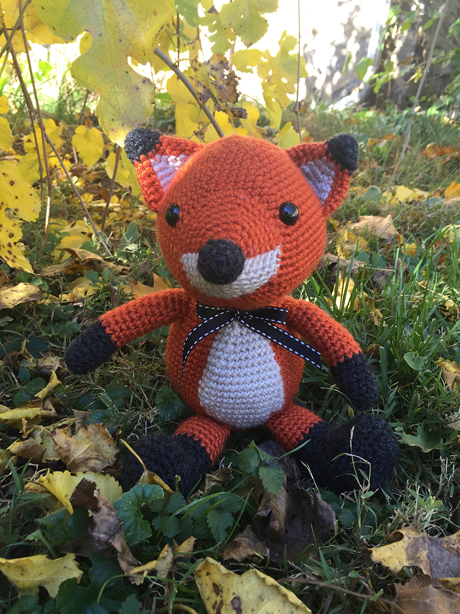 Orange and white fox sitting in the grass during autumn | Christina's Crocheted Characters