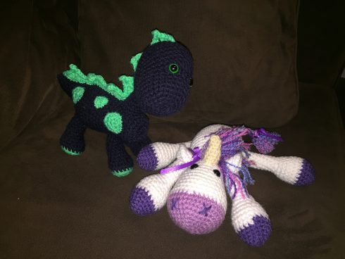 A navy and blue crocheted dinosaur standing next to a white and purple unicorn | Christina's Crocheted Characters