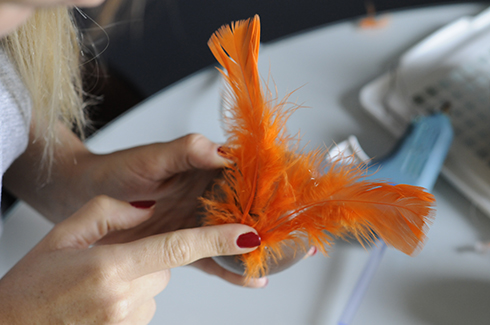 Applying orange feathers to a baseball