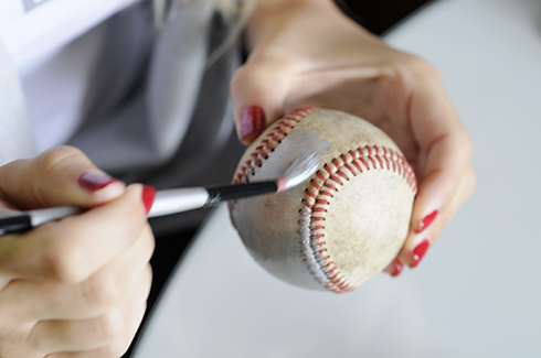 Painting a baseball with silver paint and a brush