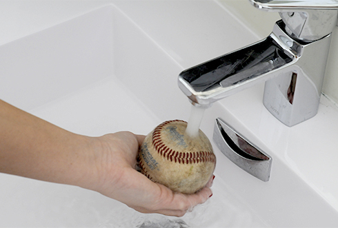 Holding a baseball under the water to clean in it preparation for arts and crafts