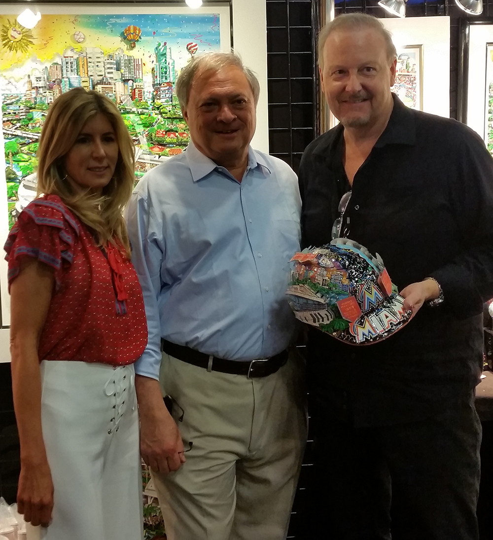 Charles Fazzino holding MLB All-Star 3D baseball helmet standing next to Marlins Owners Jeffrey and Julie Loria