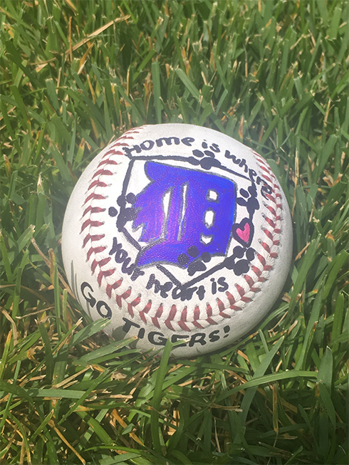 A baseball painted with a Detroit logo in purple