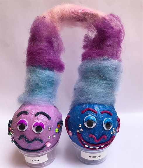 A pair of baseballs painted in blue and pink with giant fluffy hair to look like trolls