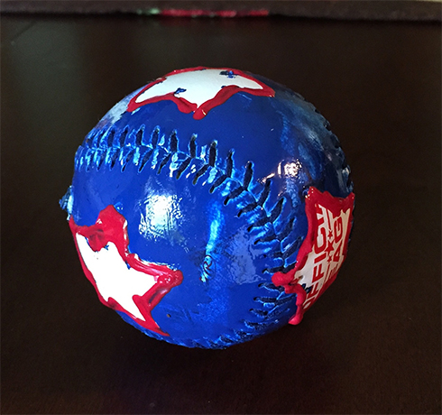 A baseball painted blue with white stars lined in red to look patriotic