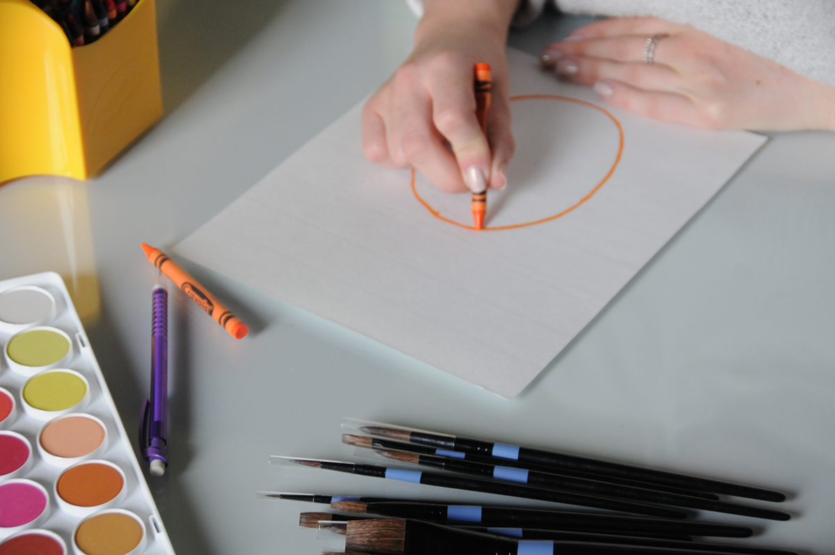 An orange circle in the shape of a pineapple being drawn on watercolor paper
