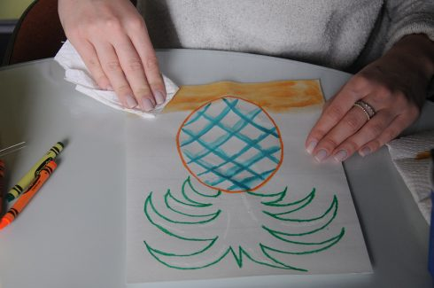 Using a paper towel to remove watercolor from a pineapple painting for a reductive effect