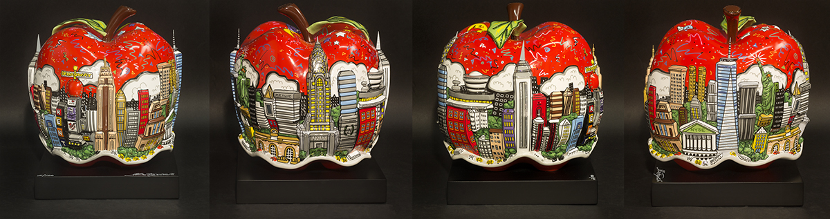 A red apple porcelain sculpture featuring the New York skyline cityscape