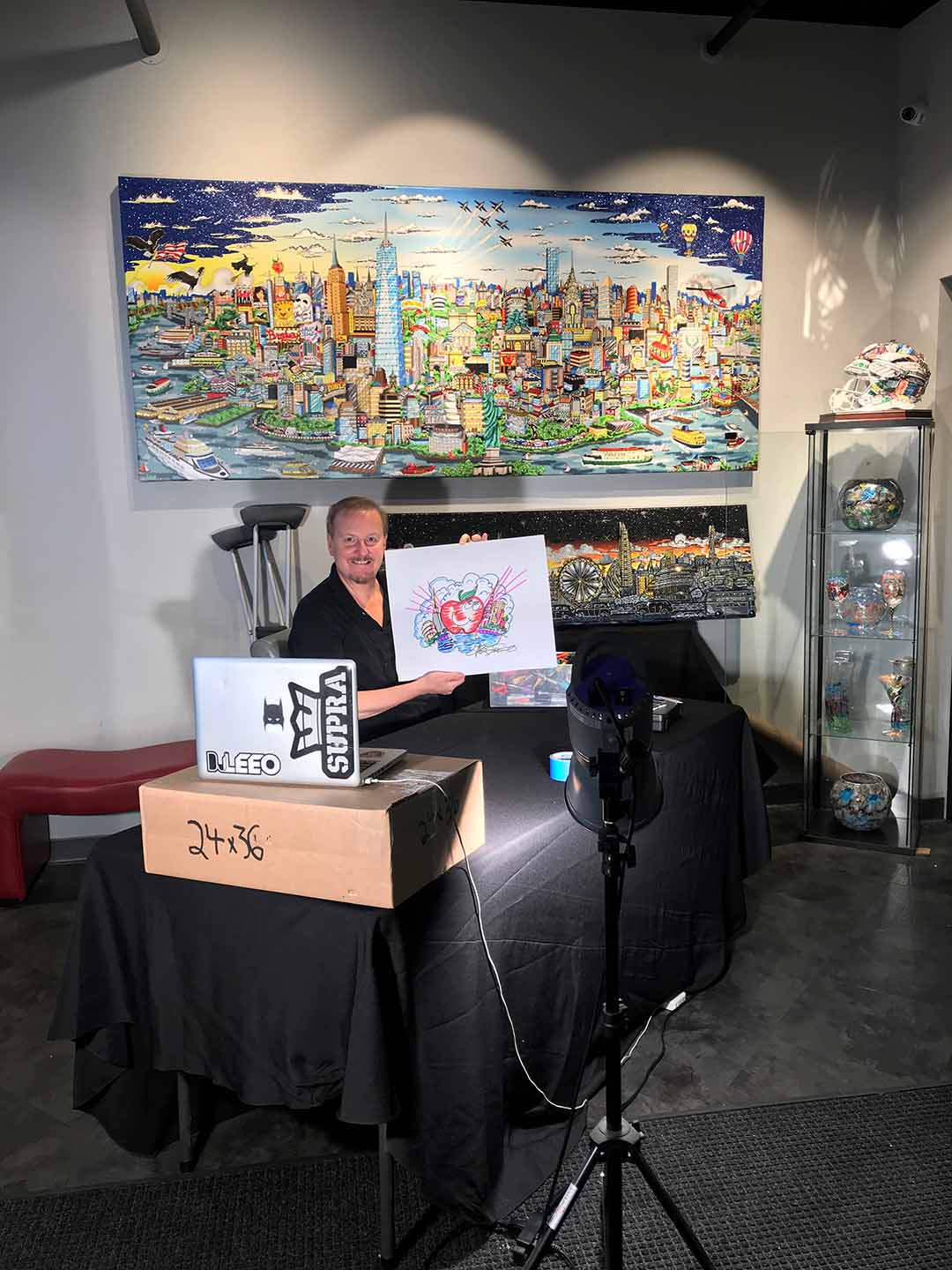 Charles Fazzino holding up a pop art doodle during his skype interview in his gallery.