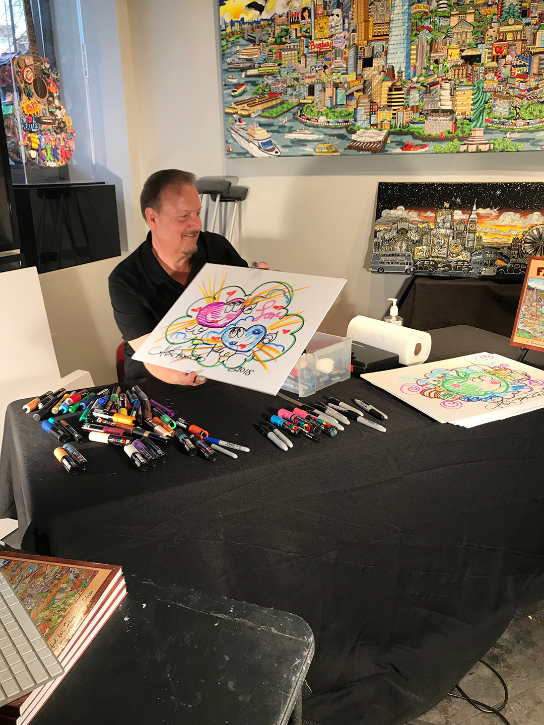 Charles Fazzino showing off a pop art doodle during his skype interview in his gallery in New Rochelle