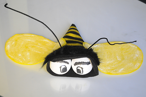 A bee made out of black and yellow felt with two baseball for the eyes