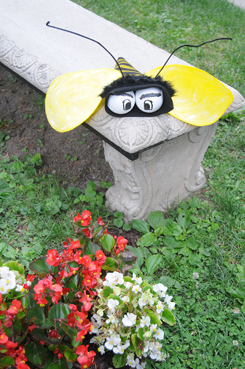A felt bee with baseballs for eyes perched on top of a stone bench in front of flowers