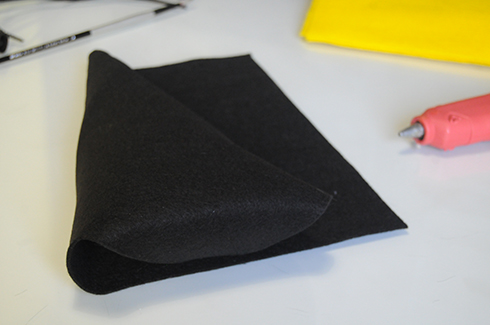 Folding black felt into a triangular shape for the body of the bee