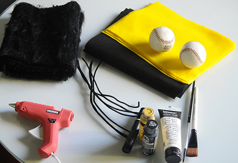 Supplies on a table including yellow and black felt, glue gun, paint, brushes for making a bee