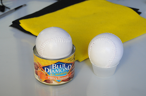 Two baseballs painted white sitting on top of a nuts can and dressing cup to dry