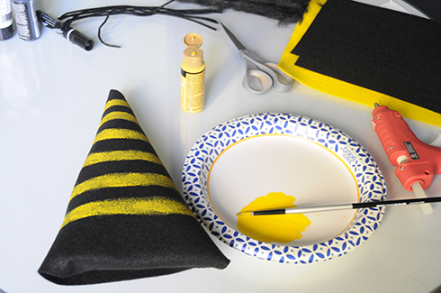 Stripes of yellow paint being applies to black felt to look like the body of a bee