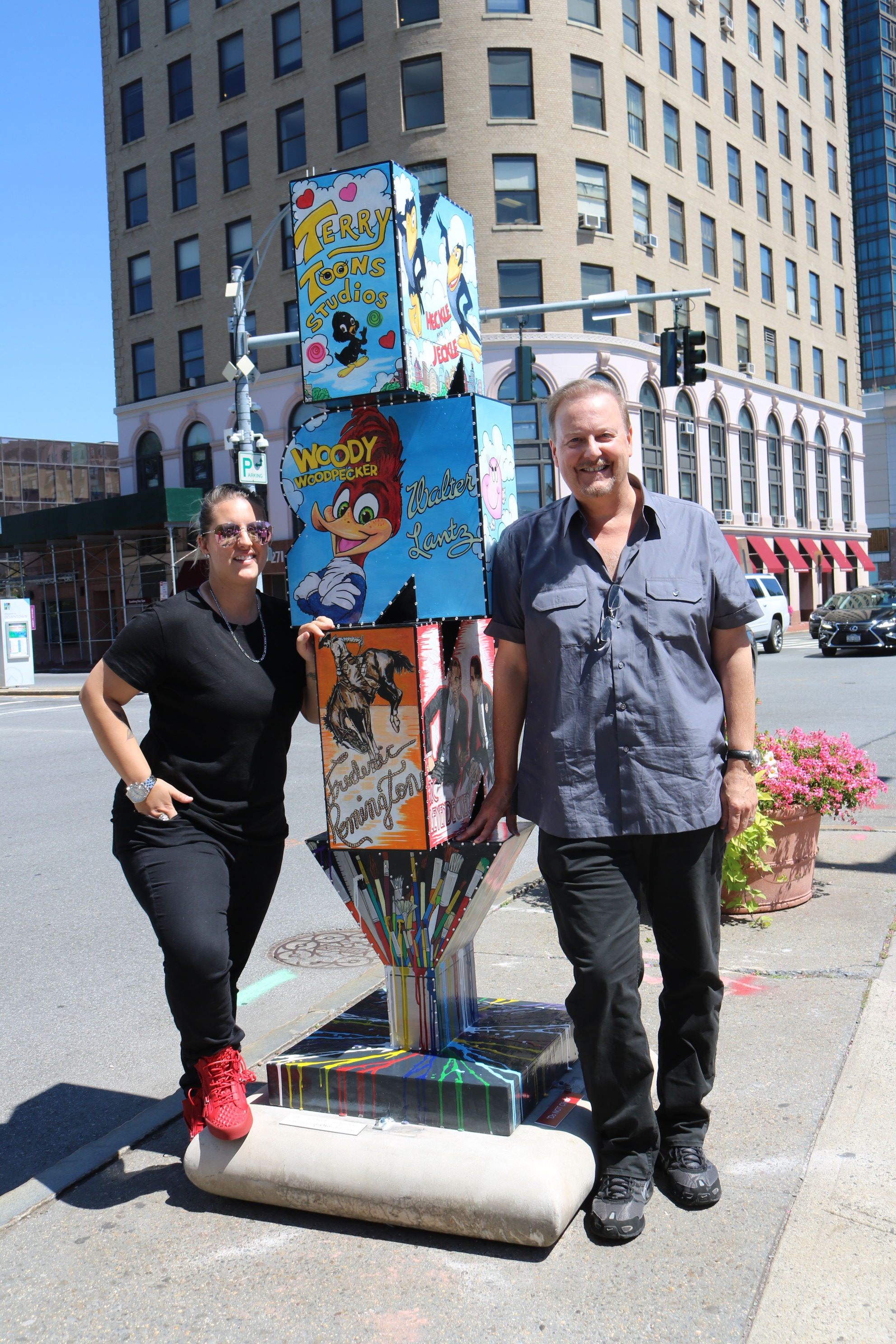 Heather and Charles Fazzino standing next to Charles' pop art New Rochelle sculpture
