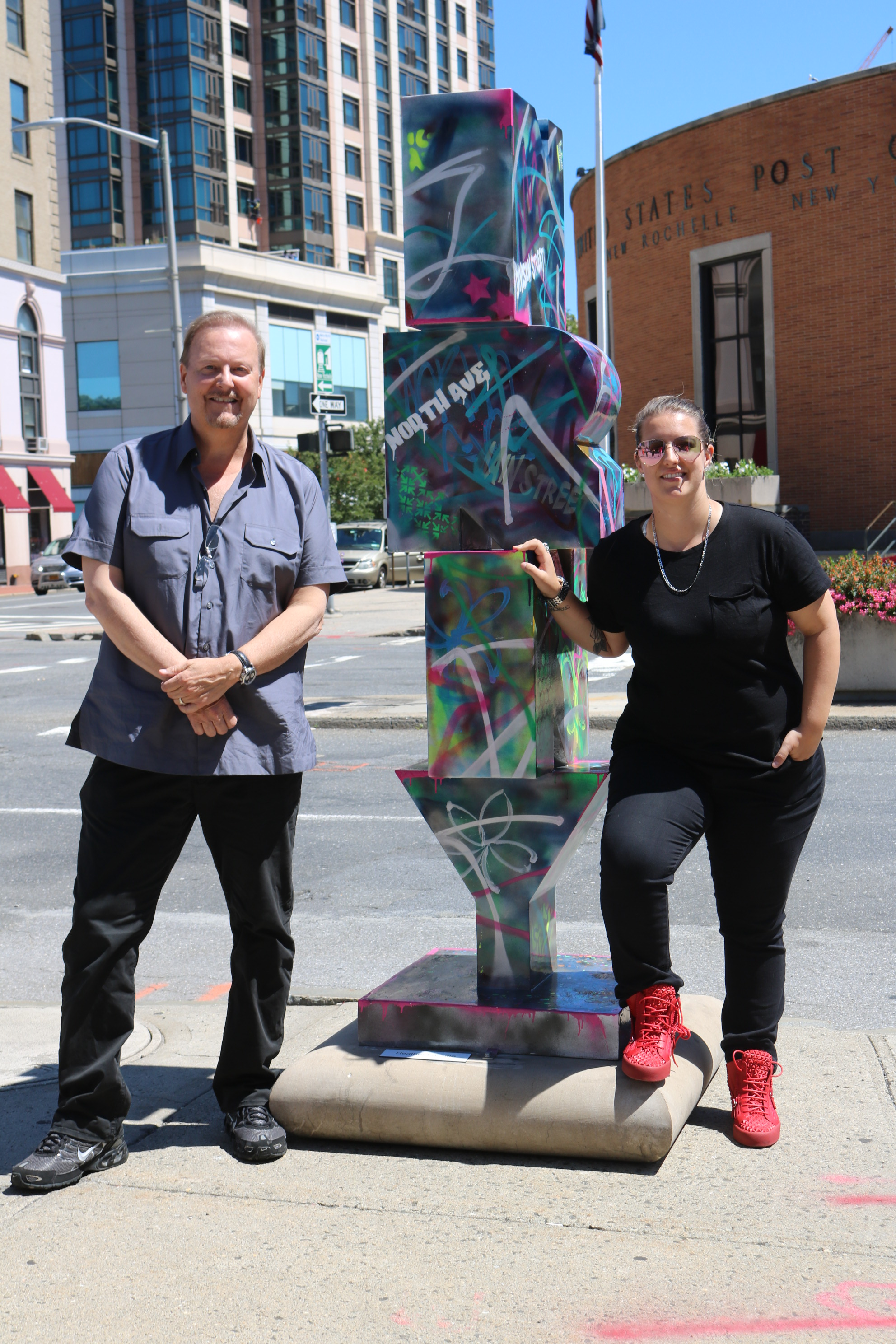 Heather and Charles Fazzino standing next to Heather's graffiti inspired New Rochelle sculpture