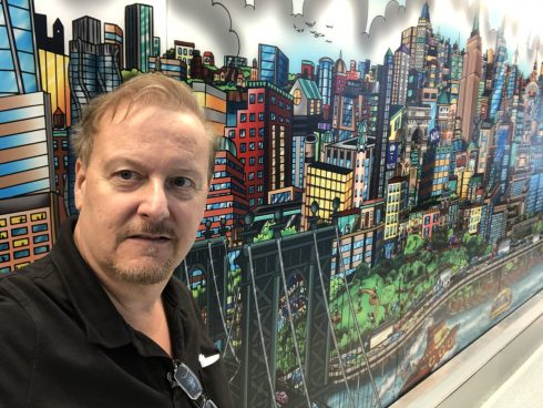 Charles Fazzino taking a selfie in front of his New York City Mural in NYU Langone Health