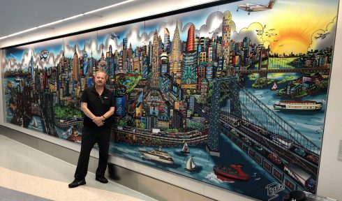 Charles Fazzino standing in front of a 3D pop art mural of a New York City skyline in NYU Langone Health