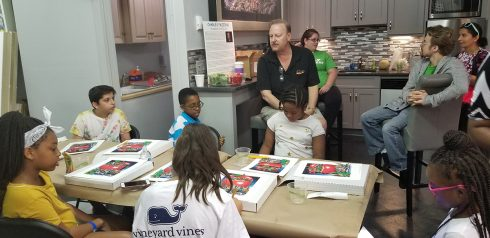 "Charles Fazzino sitting on a stool in the Fazzino Art Studio kitchen talking to ""It Takes a Village to Educate a Child"" students before they start their art project."