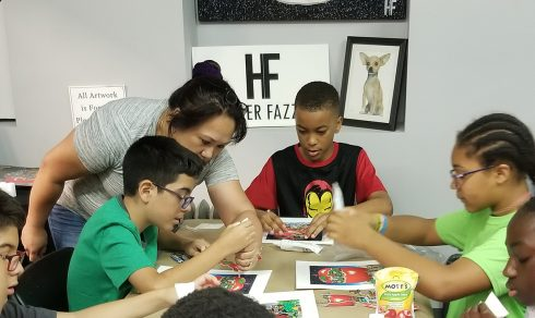 "Sonia Marshall-Brown from ""It Takes a Village to Educate a Child"" program helping her students with a Charles Fazzino art project"