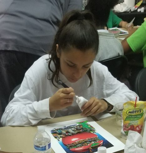 A young girl with brown hair pulled back in a ponytail using glue to help create her Fazzino 3D pop art piece