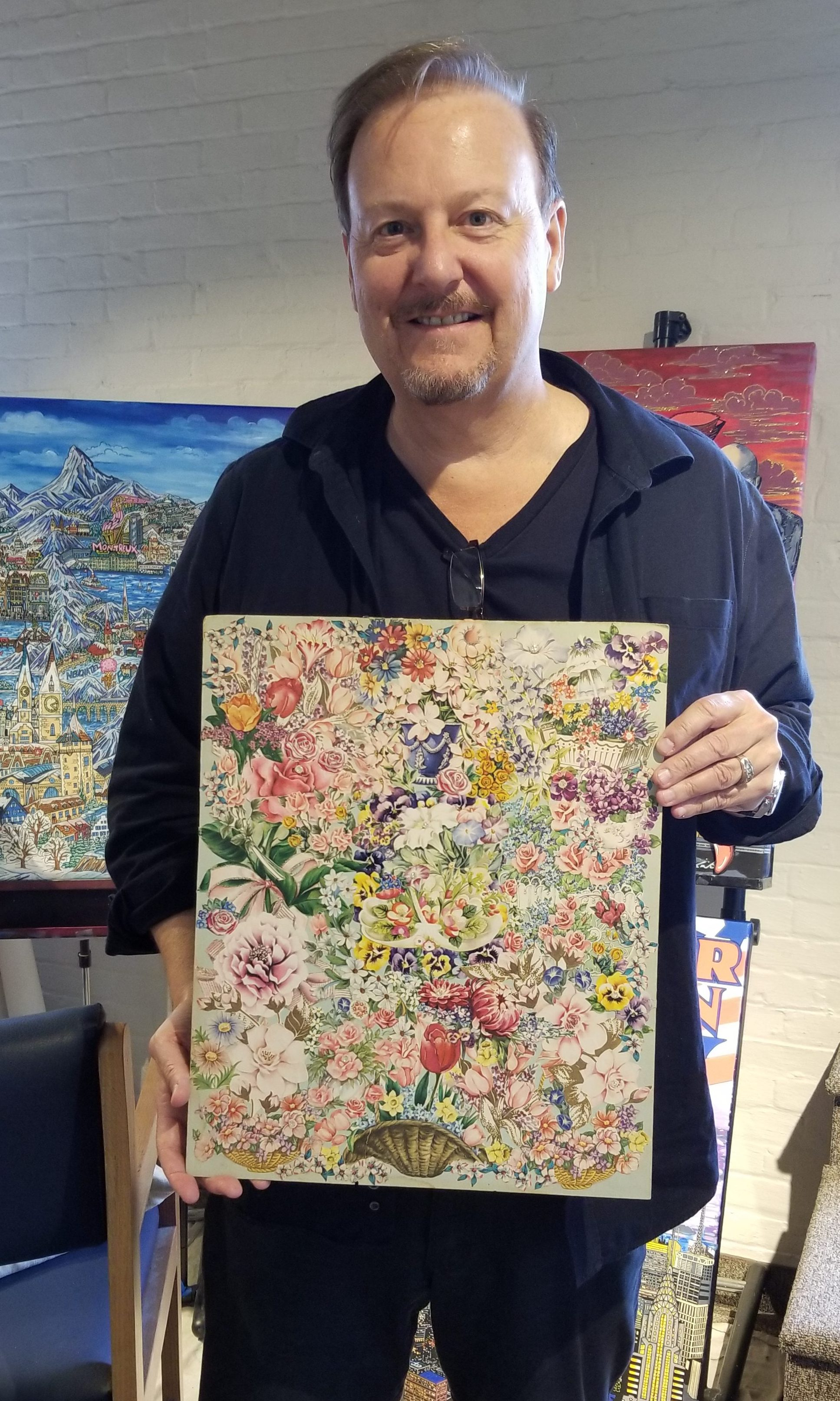 Charles Fazzino standing up holding a multi-colored floral art piece