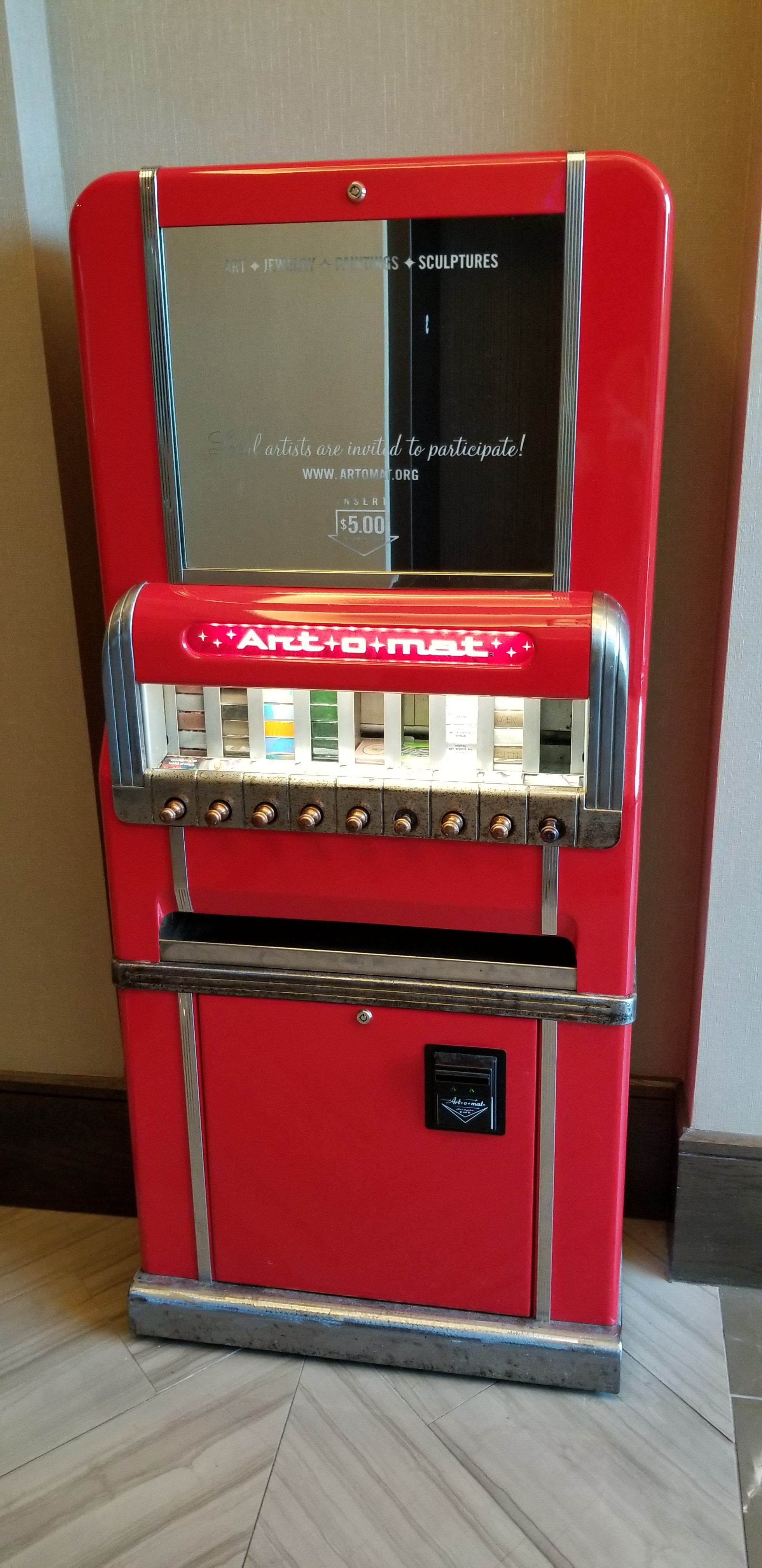 Red Art-O-Mat machine that looks like an old fashioned cigarette vending machine that sells art work