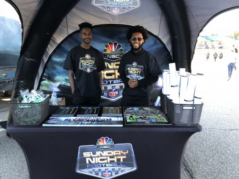 Hanging out at the Sunday Night Football booth with art posters by Fazzino and brochures and giveaways