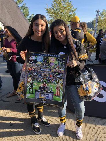 Two Sunday Night Football fans dressed in uniforms holding a Fazzino poster are all smiles at the event