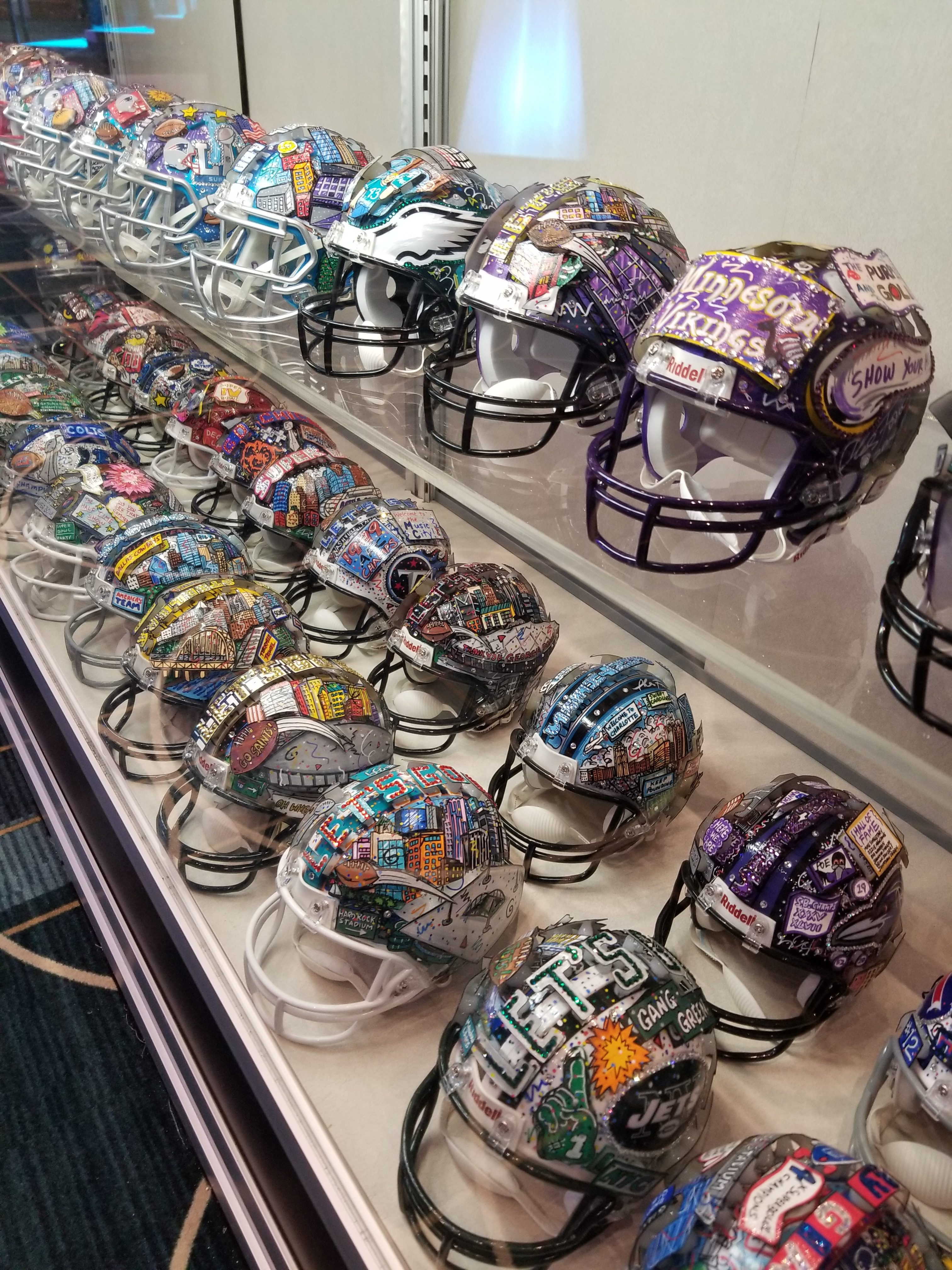 The hand painted Fazzino mini football helmet art collection on display at the NFL Experience