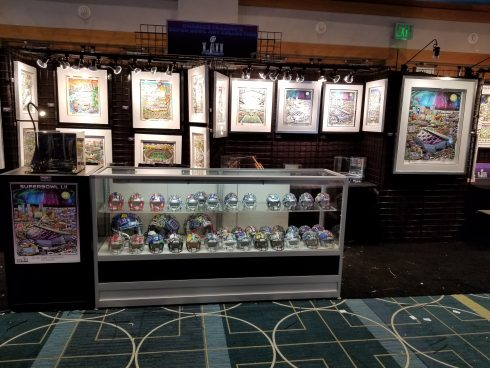 The Fazzino Super Bowl booth featuring framed artwork, mini football helmets and poster art