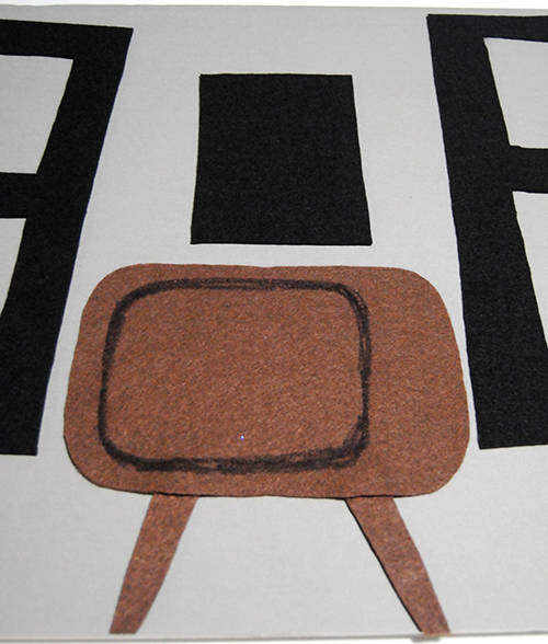 A vintage television cut out of brown felt on a grey paper board