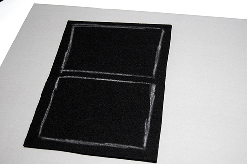 A piece of black felt on a grey paper board with chalk drawings to mark out a window