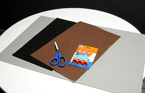 Grey paper board, brown and black felt, scissors and glue stick supplies on a white table