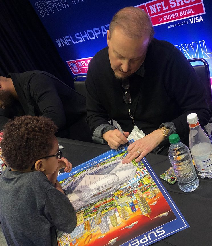 Charles Fazzino signing a Super Bowl LIII poster for a young football fan at the NFL Shop in Atlanta