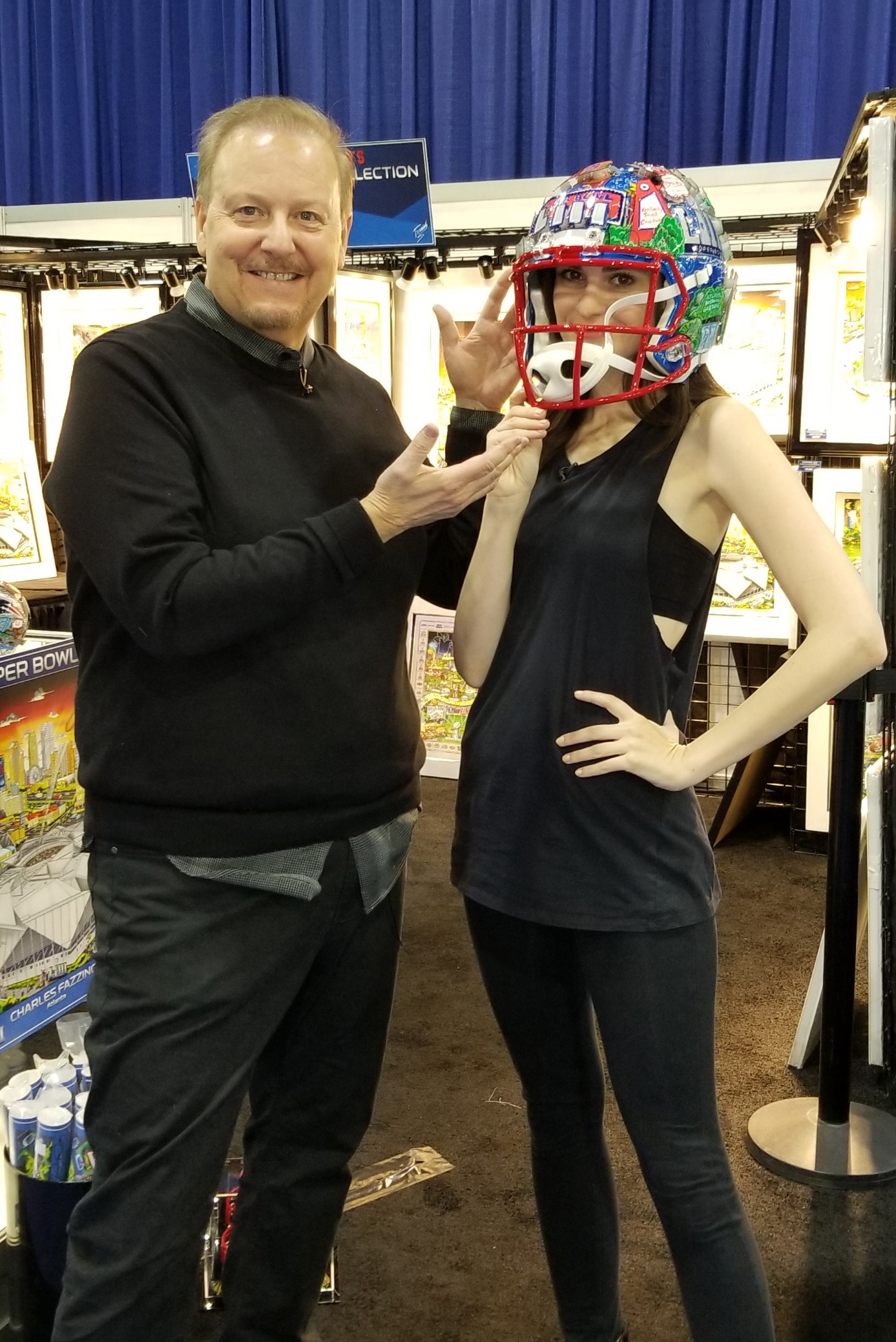 Charles Fazzino puts the Super Bowl LIII helmet on Kelleth Cuthbert's head as they stand in front of the NFL Experience booth